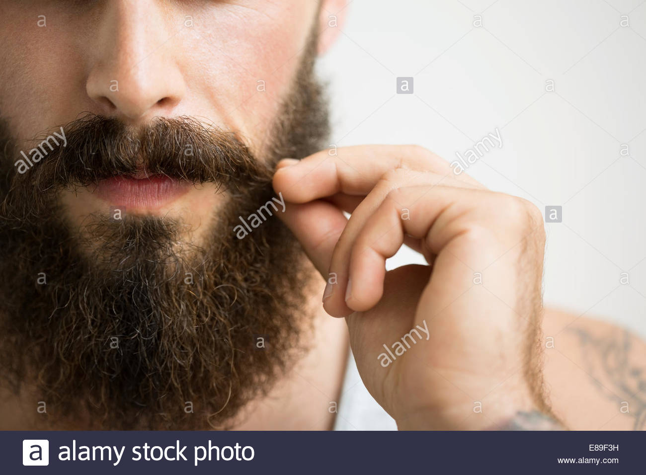 Close up of man touching mustache - Stock Image