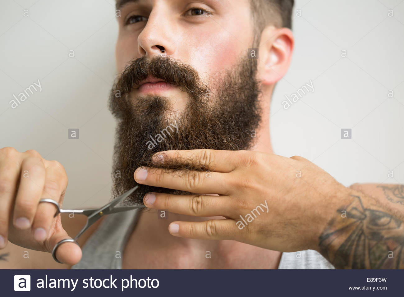 Close up of man trimming beard with scissors - Stock Image