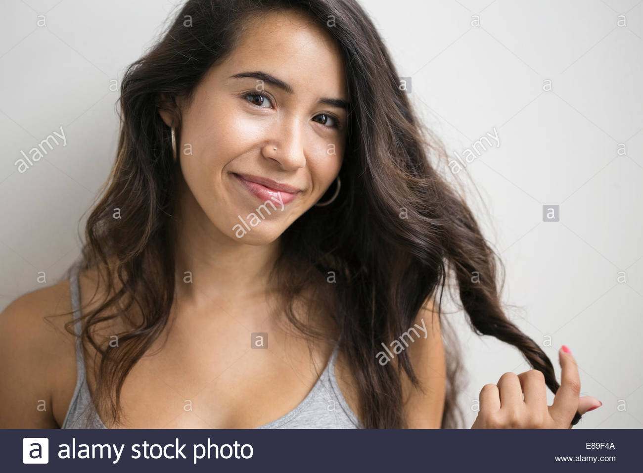 Portrait of smiling young brunette woman twirling hair - Stock Image