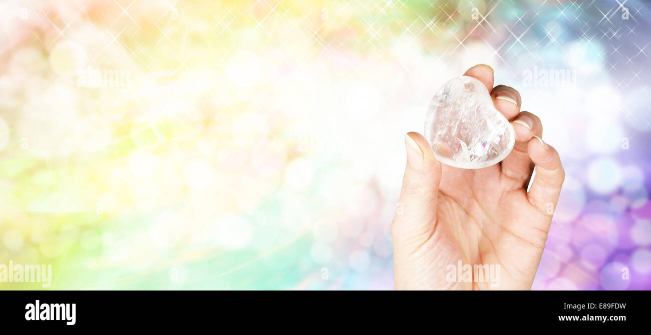Crystal Healer holding large clear quartz puff heart crystal on sparkles and rainbow colored bokeh background Stock Photo