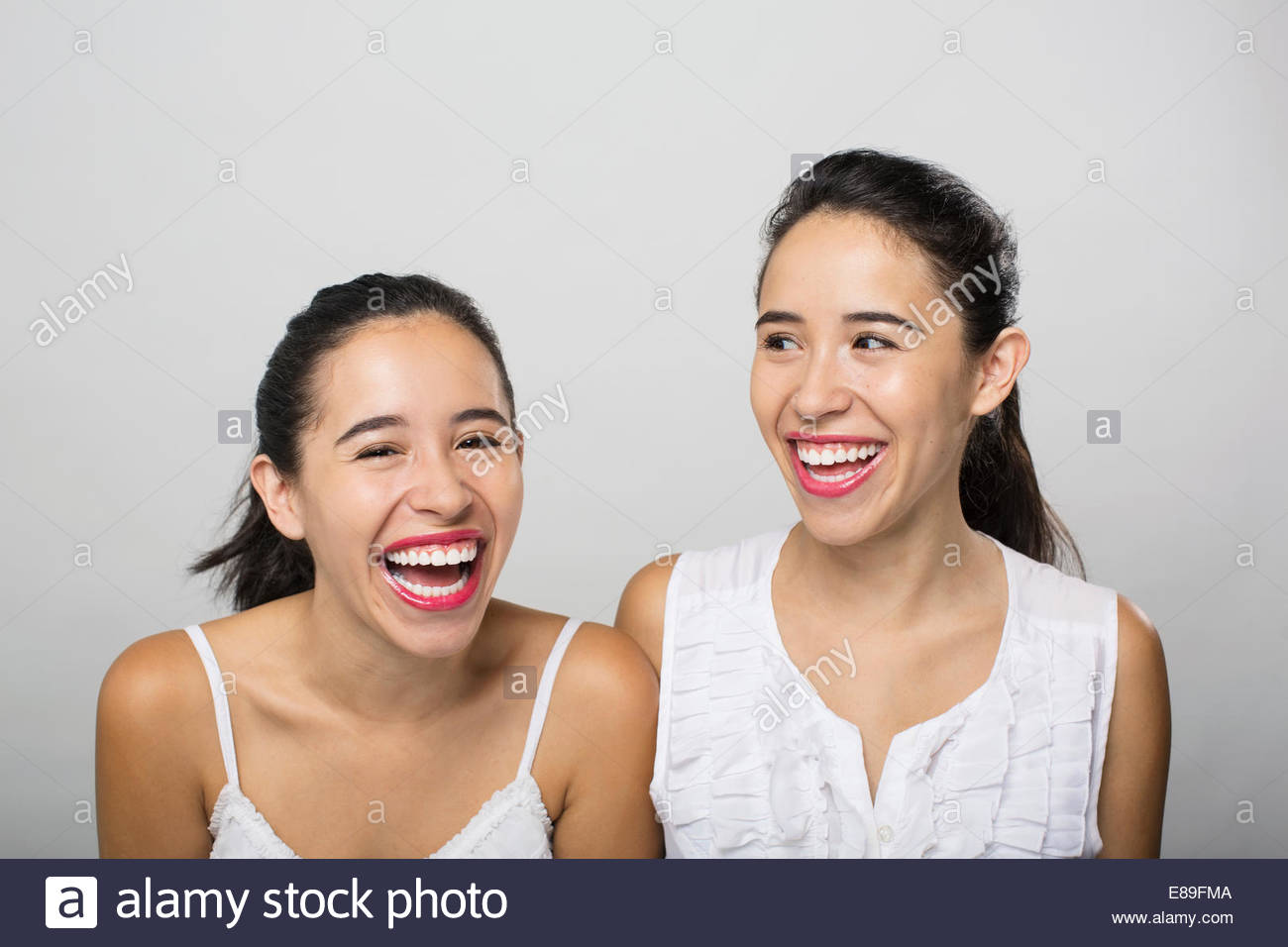 Brunette twin sisters laughing - Stock Image