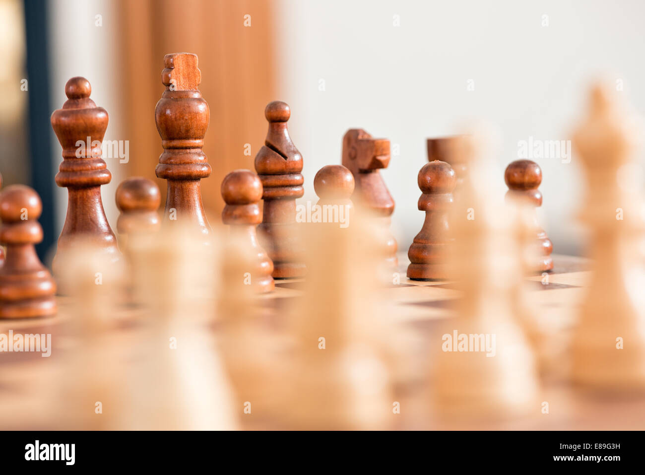 Wooden chess pieces facing off, across the games board during a match - Stock Image