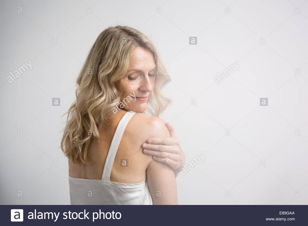 Blonde woman touching shoulder - Stock Image