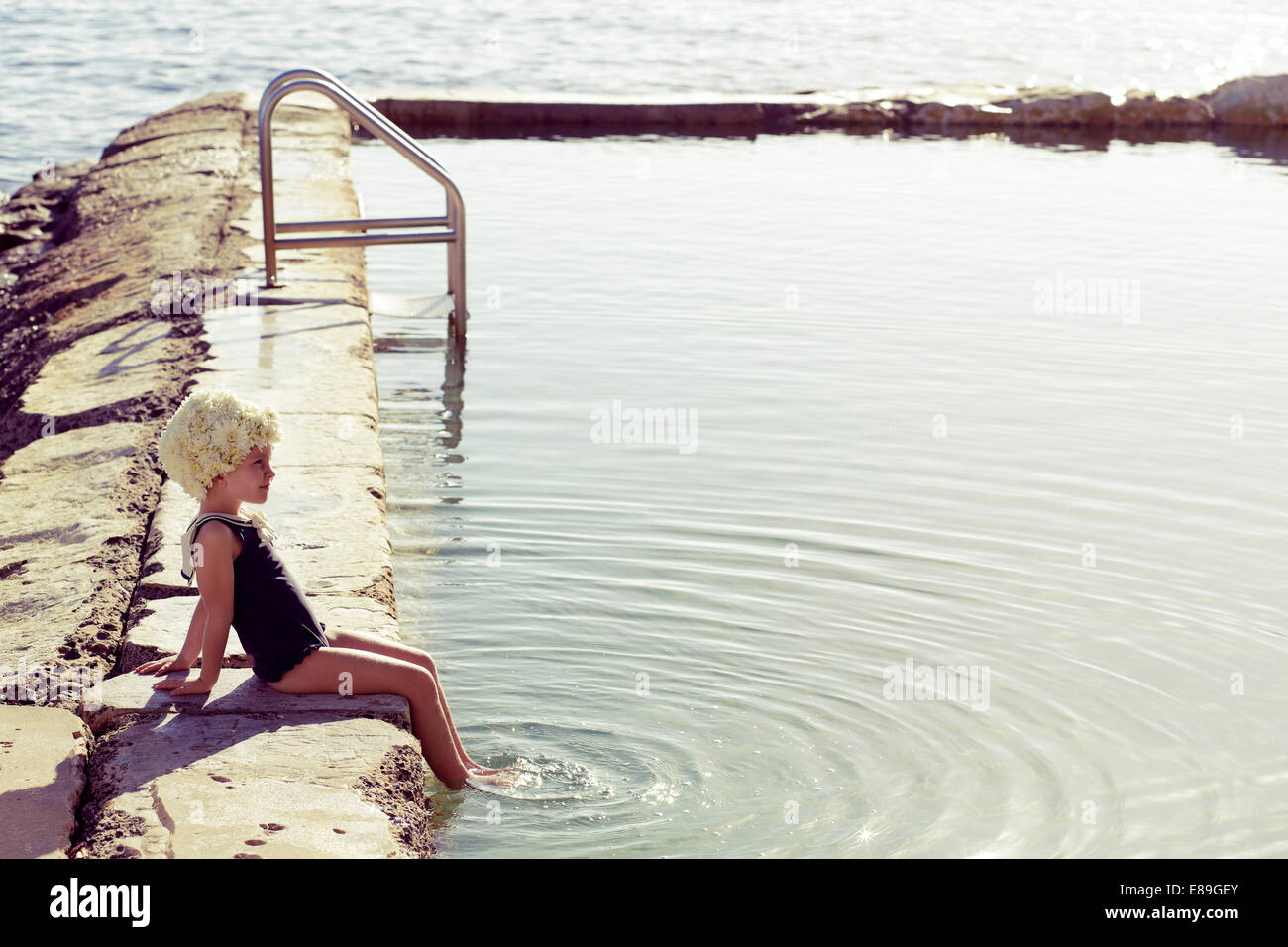 Girl in Flower cap sitting along pool - Stock Image