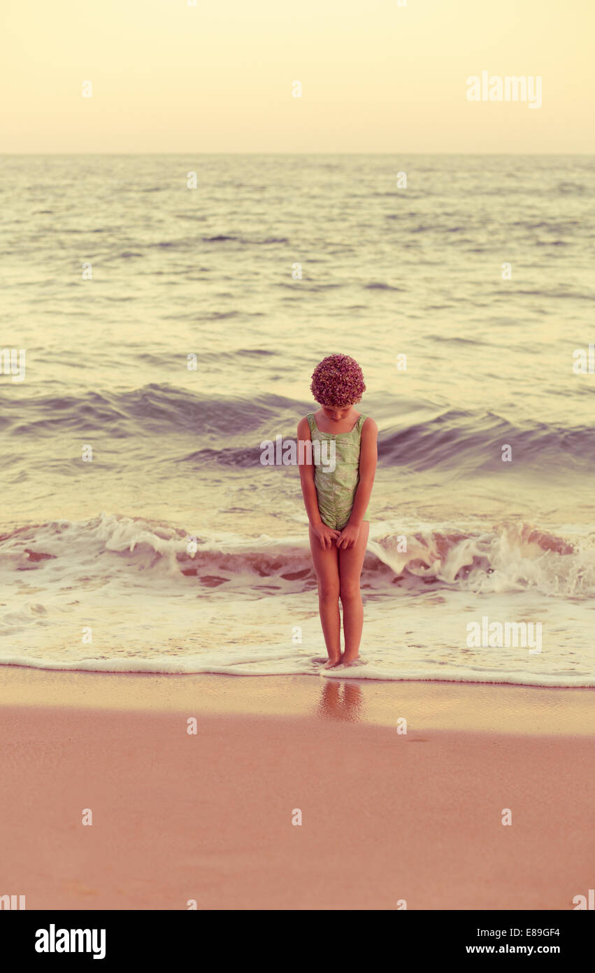 Girl in swimcap standing in the waves - Stock Image