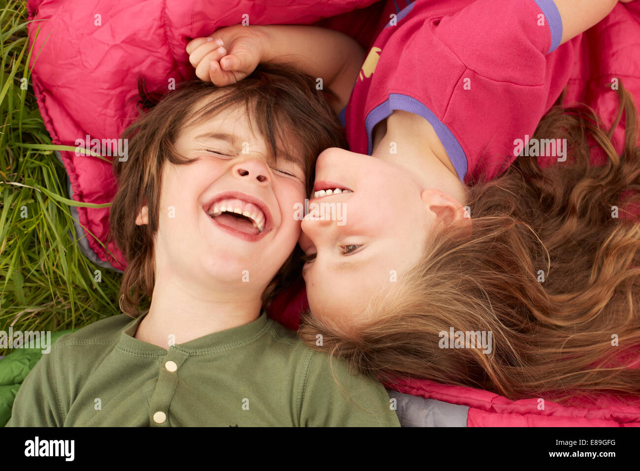 Boy and Girl laughing while laying on sleeping bags - Stock Image