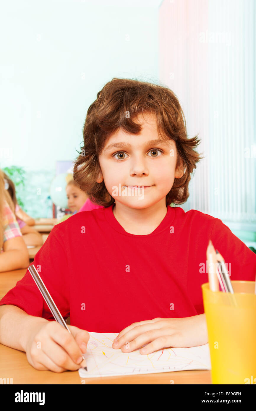 Boy looking straight and writing in exercise book - Stock Image