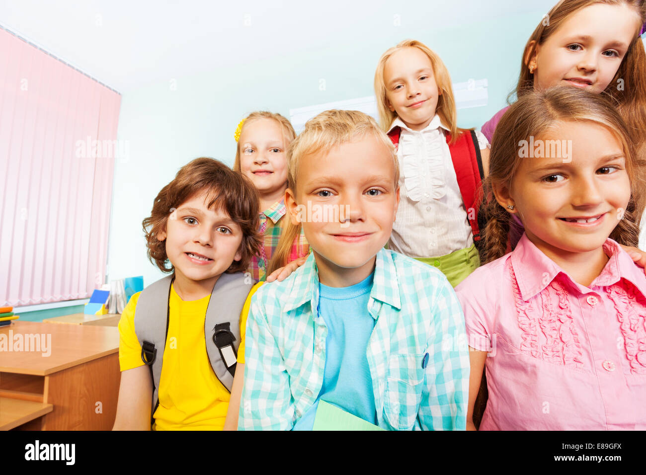 Kids sit near desk and smile in classroom - Stock Image