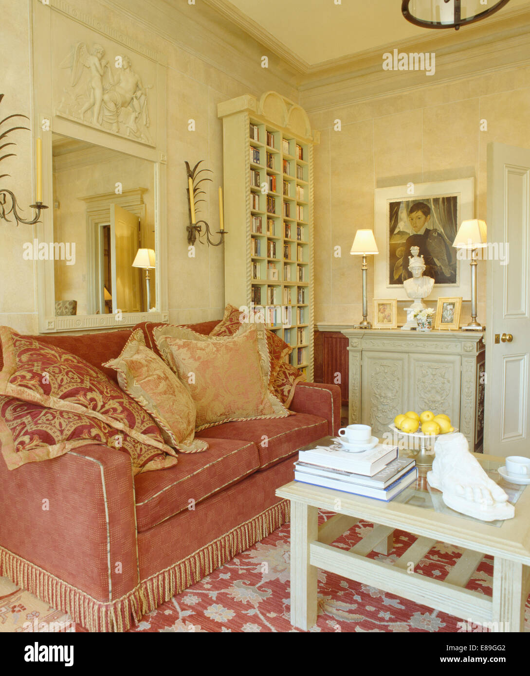 Carved mirror above patterned cushions on dark red sofa with ...