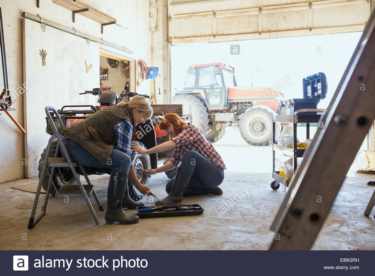 Mother and daughter repairing quadbike wheel - Stock Image