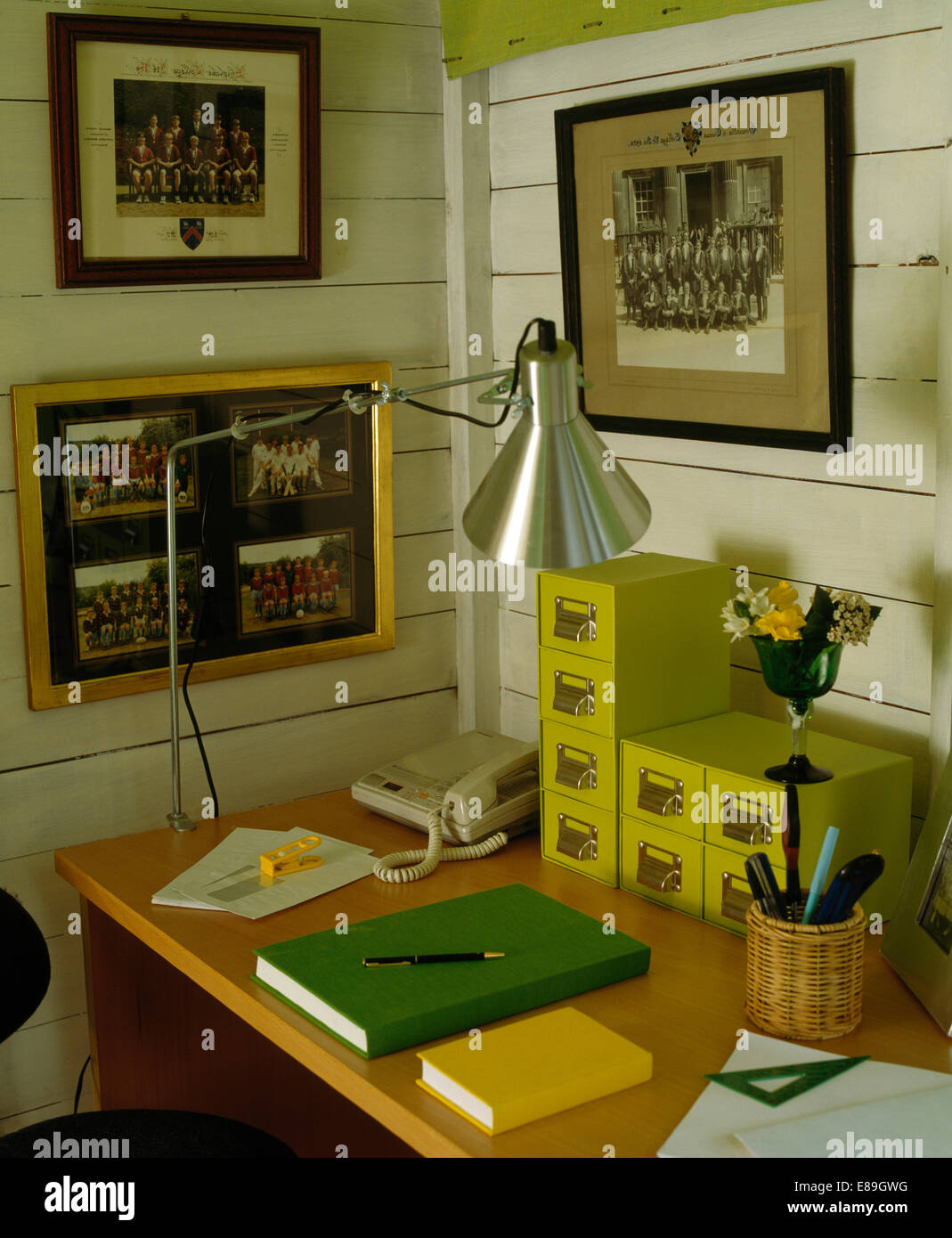 Framed photographs on walls above desk with small yellow