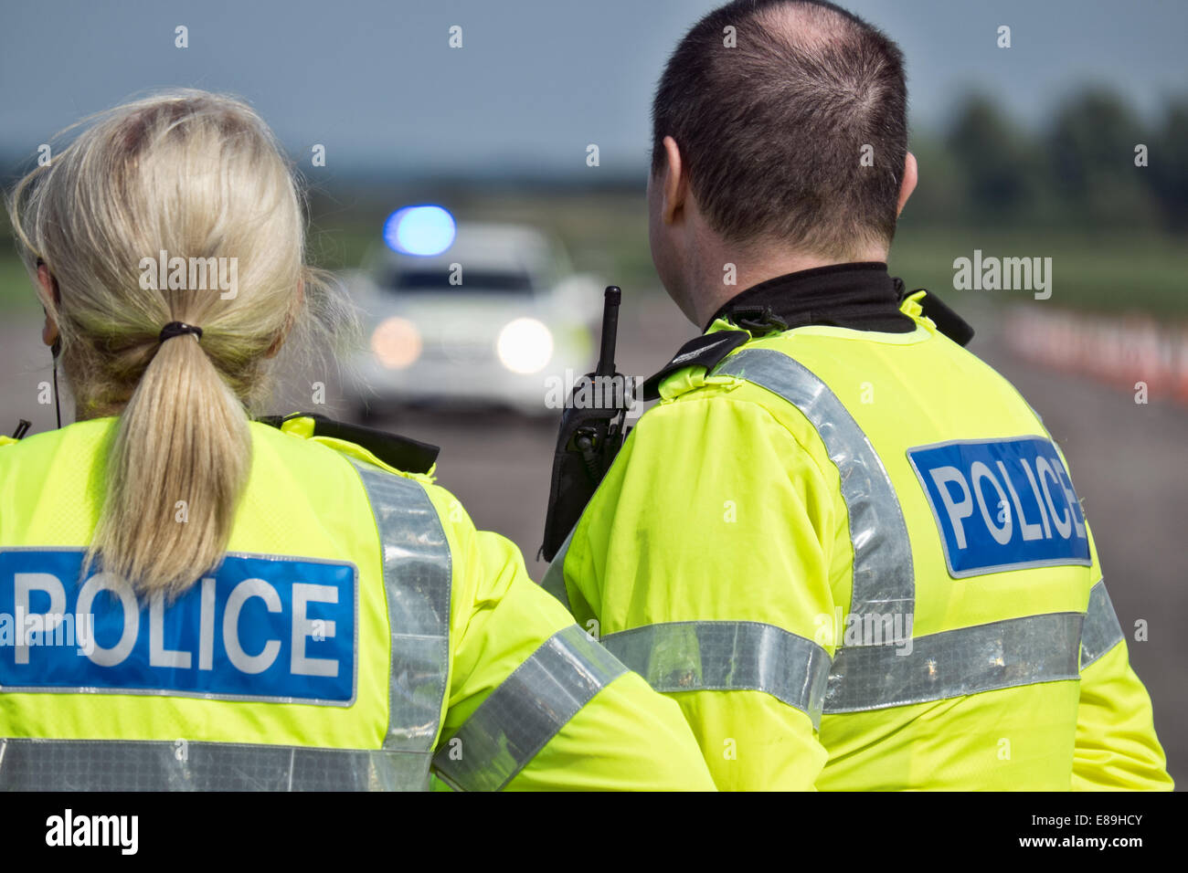 Uniformed British Police officers awaiting the arrival of their colleagues at an incident - Stock Image