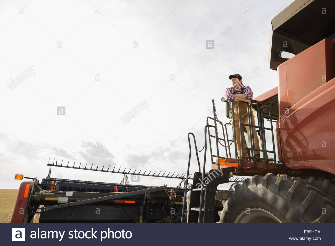 Farmer on platform of combine harvester - Stock Image