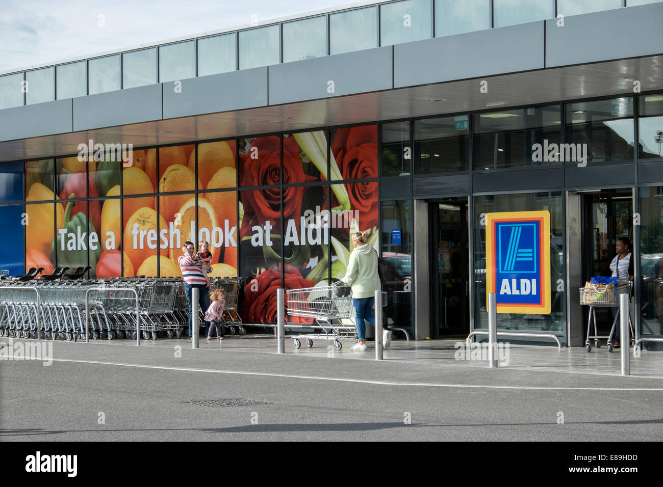 Customers & shopping carts outside German discount supermarket, Aldi in Swindon, Wiltshire, UK - Stock Image
