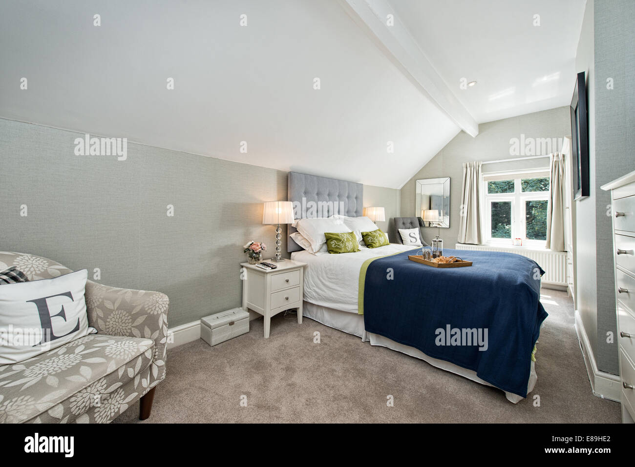 Breakfast in bed in a comfortable contemporary double bedroom decorated in blues & greys - Stock Image