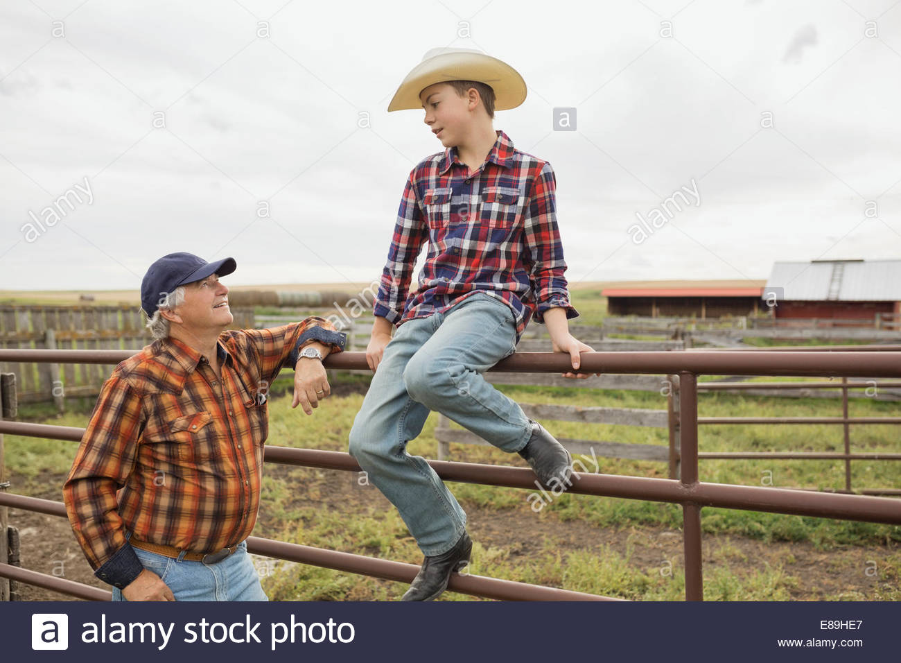 Grandfather and grandson talking at farm fence - Stock Image