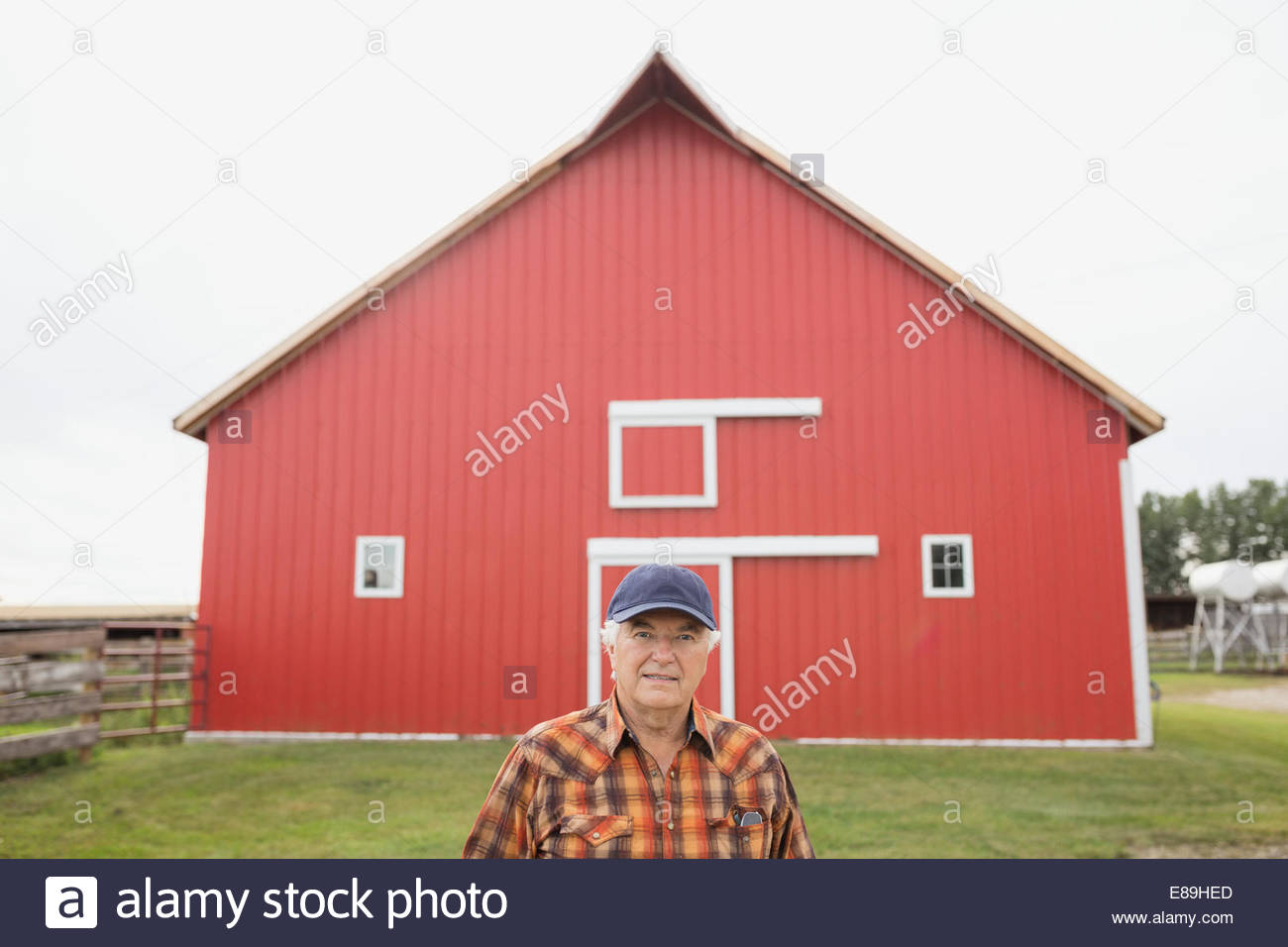 Farmer standing in front of red barn - Stock Image