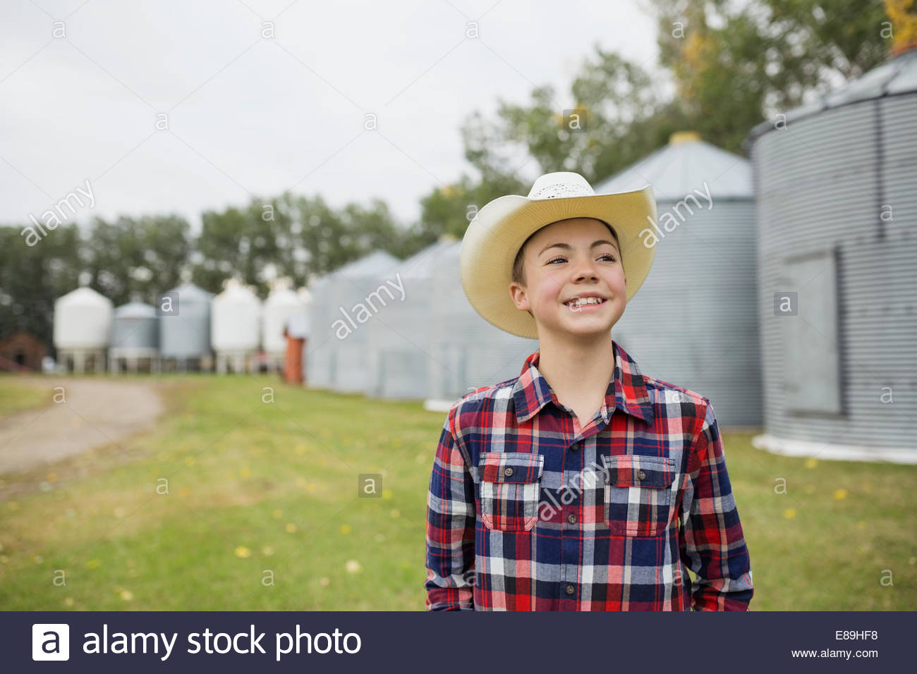 Boy in cowboy hat smiling on farm - Stock Image