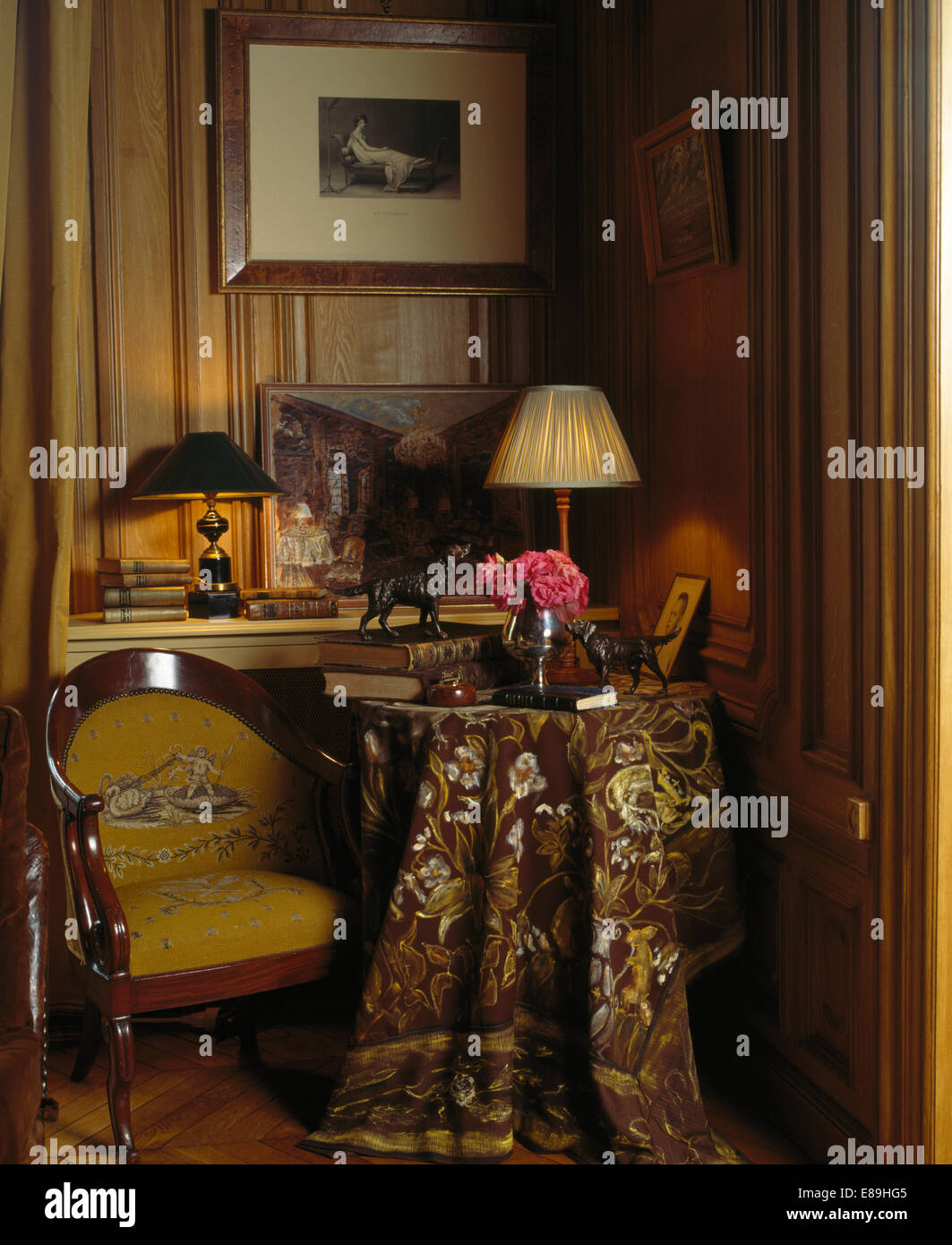 Antique chair and small table with lighted lamp and richly patterned cloth in corner of wood paneled study - Stock Image