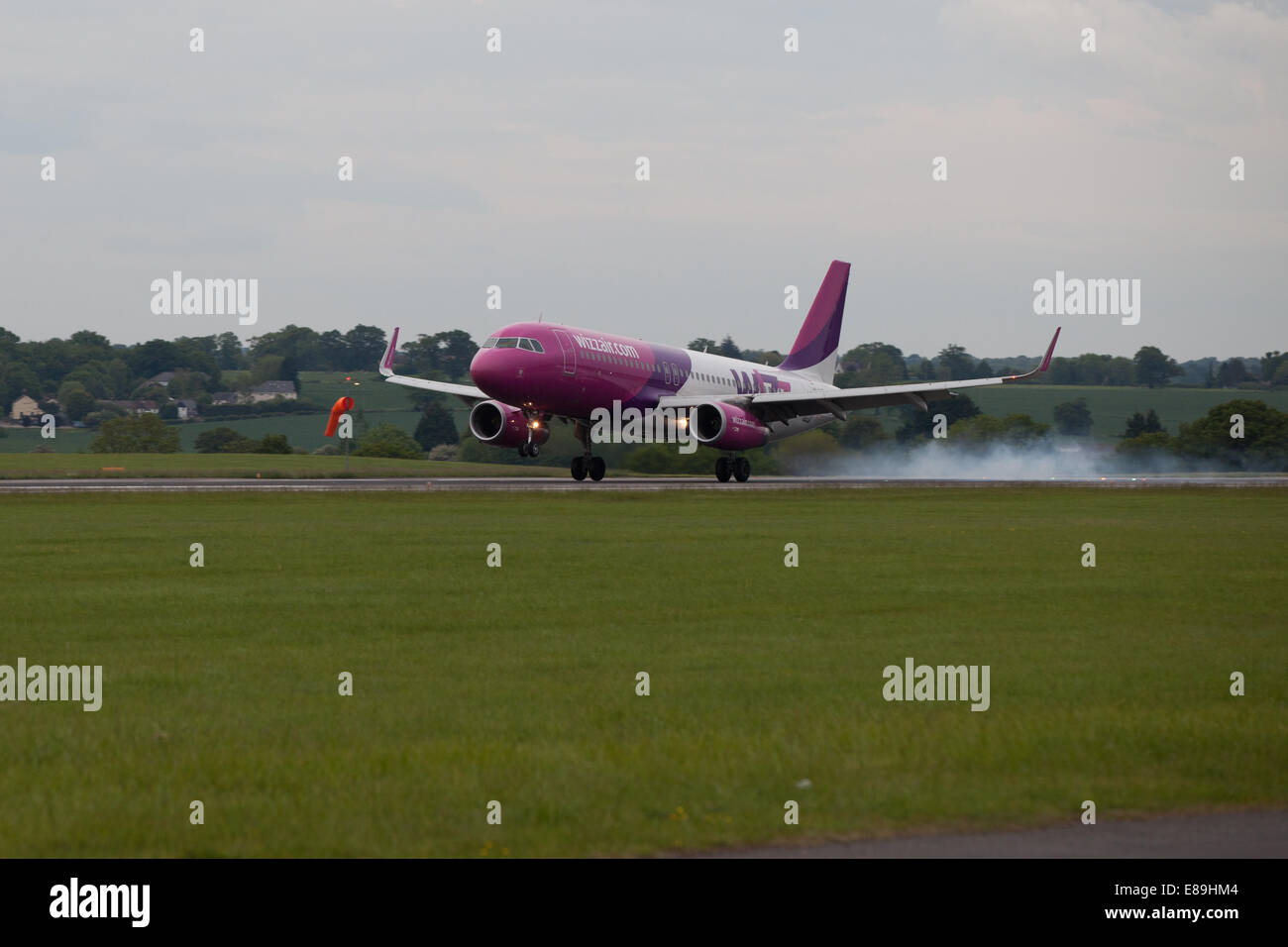 Wizzair airliner generates wheel smoke landing at Luton - Stock Image