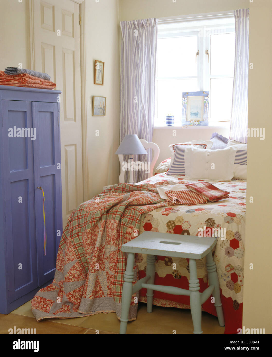 Painted stool below bed with patchwork quilt and floral ...