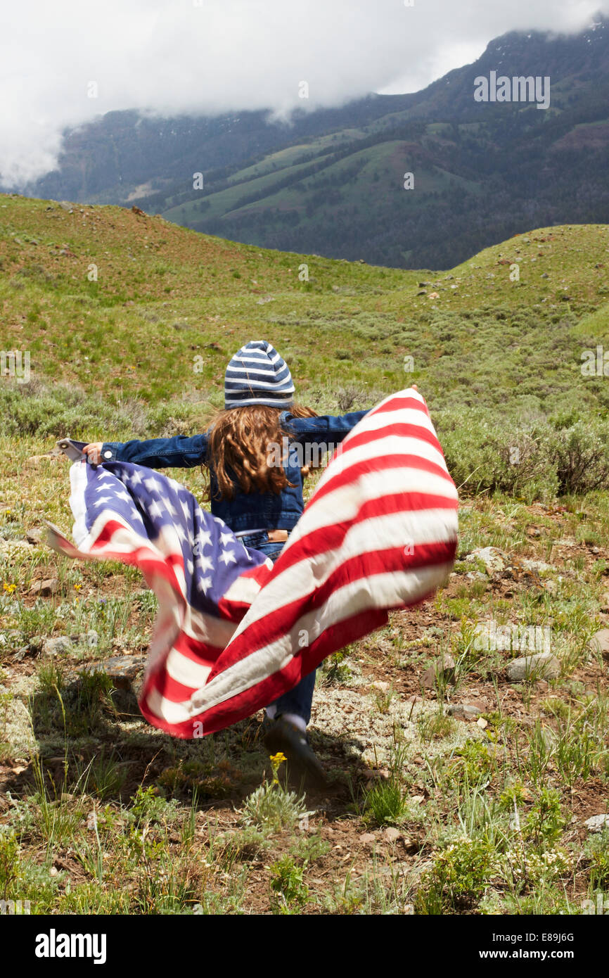 Girl wrapped in American Flag in field - Stock Image