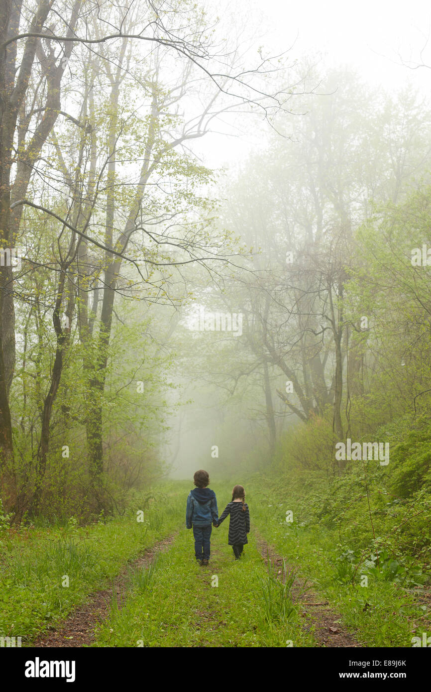 Brother and sister walking down foggy path - Stock Image