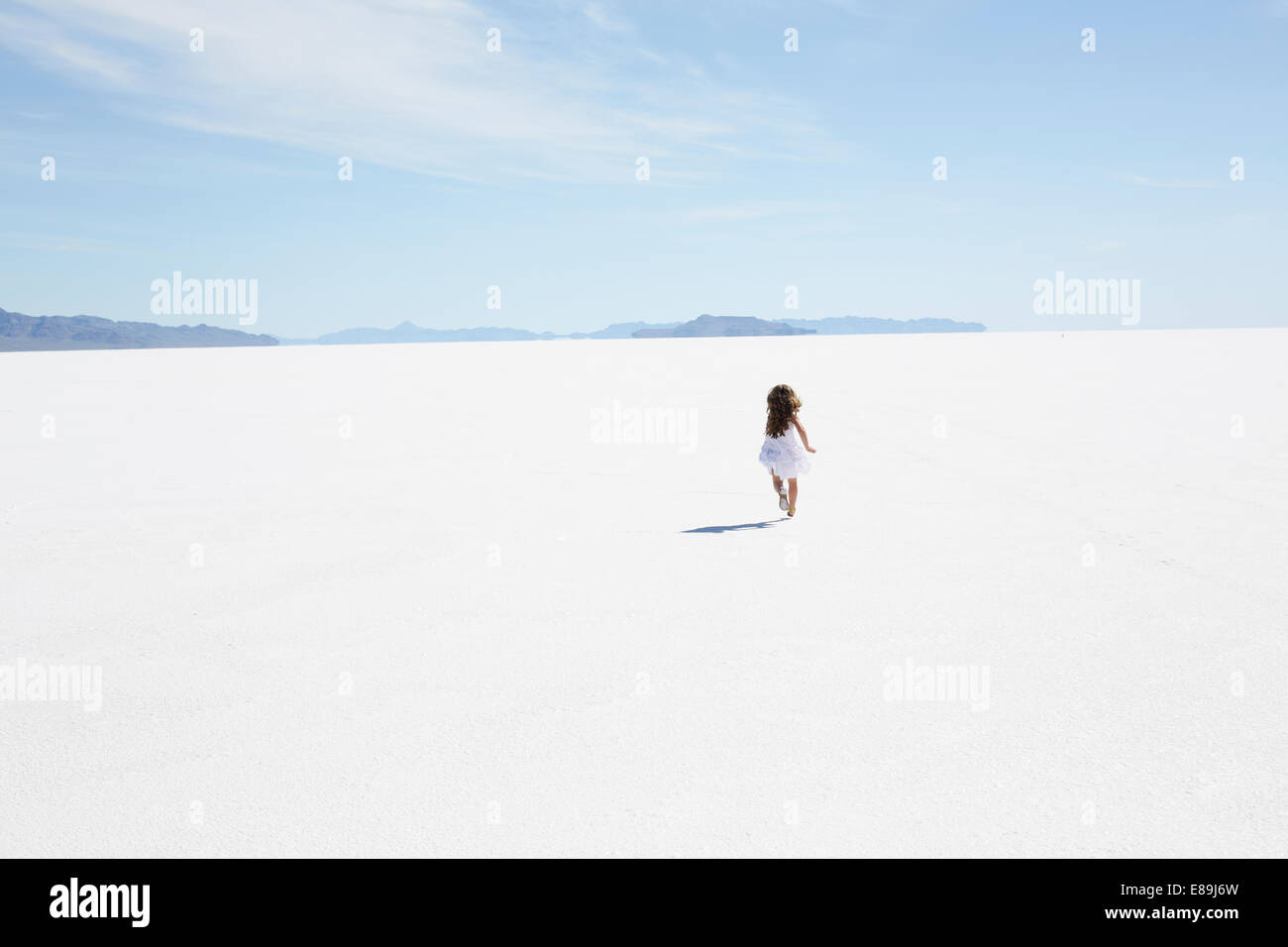 Girl running along Bonneville Salt Flats - Stock Image