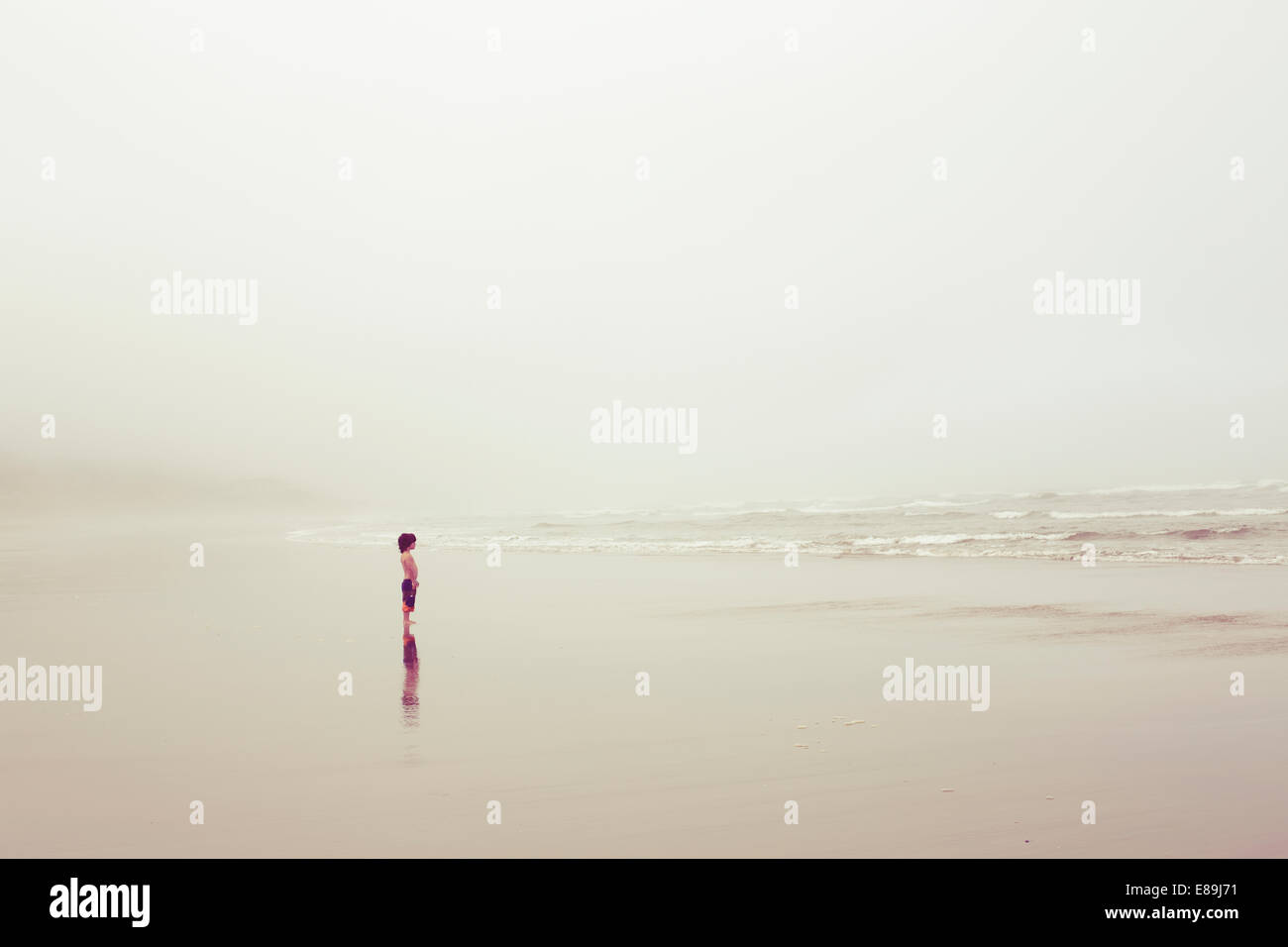 Boy at the ocean on overcast day Stock Photo