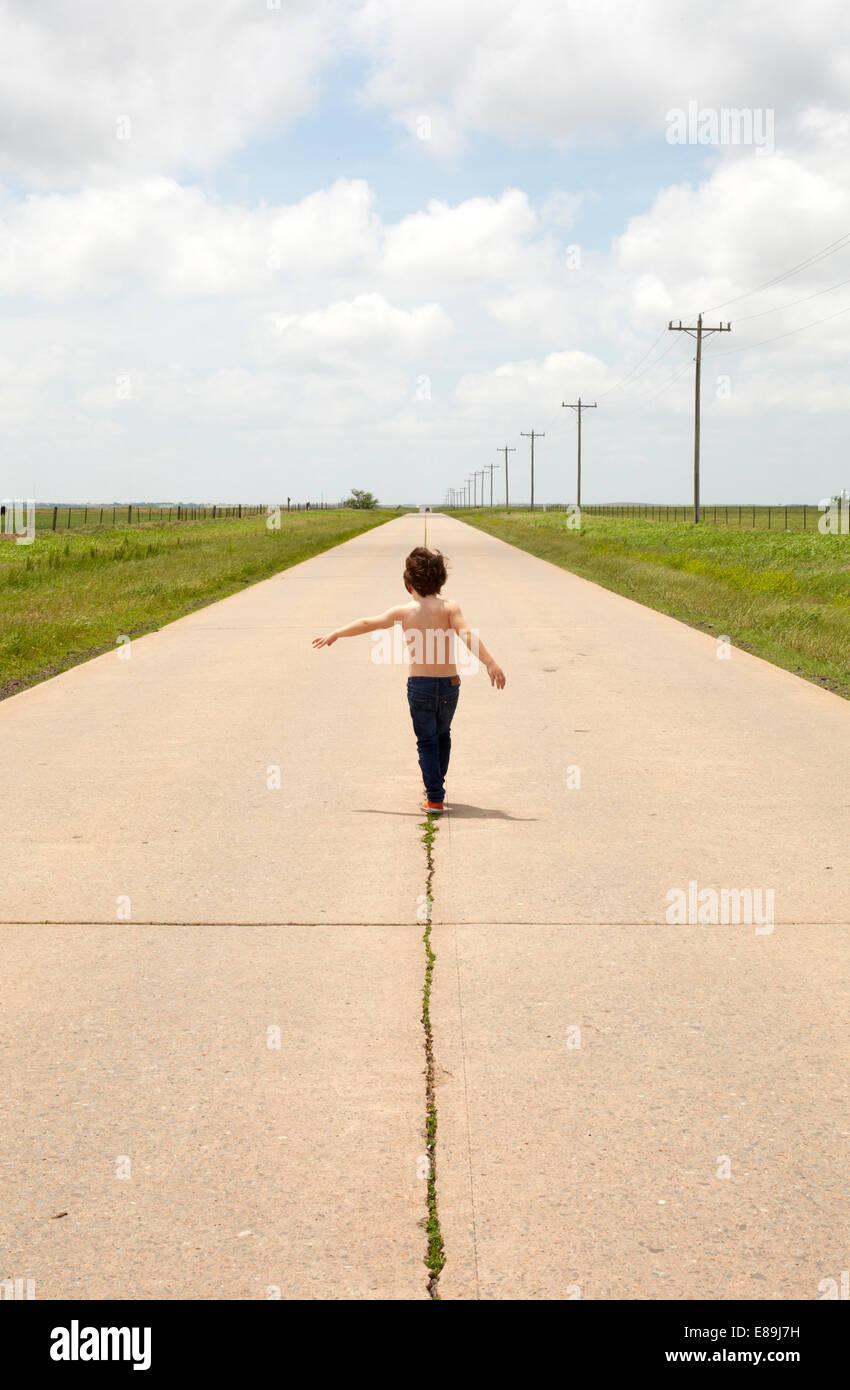 Boy walking along sidewalk in country - Stock Image