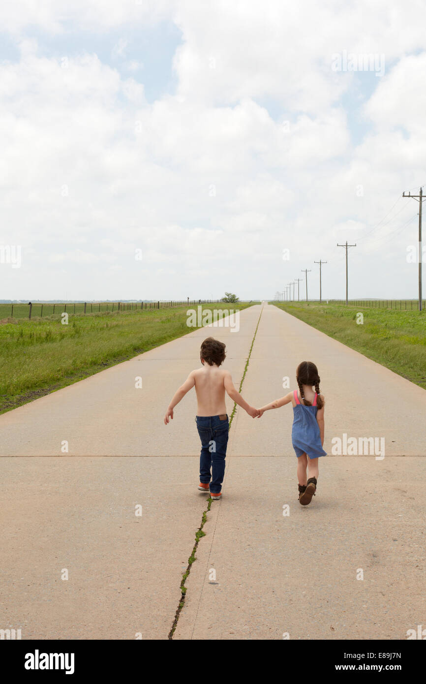 Brother and sister walking along sidewalk in country - Stock Image