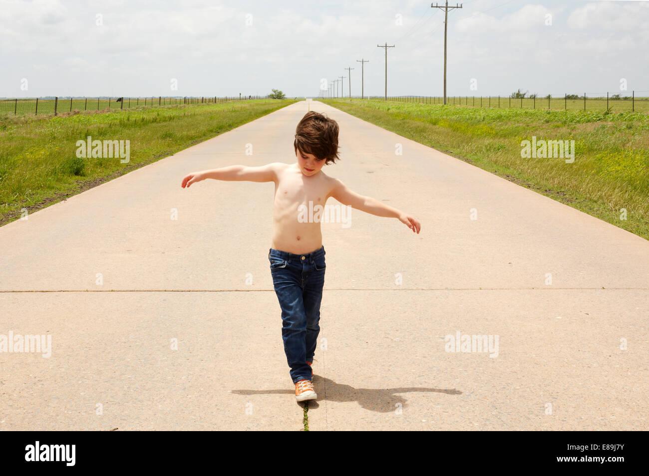 Boy walking along sidewalk - Stock Image