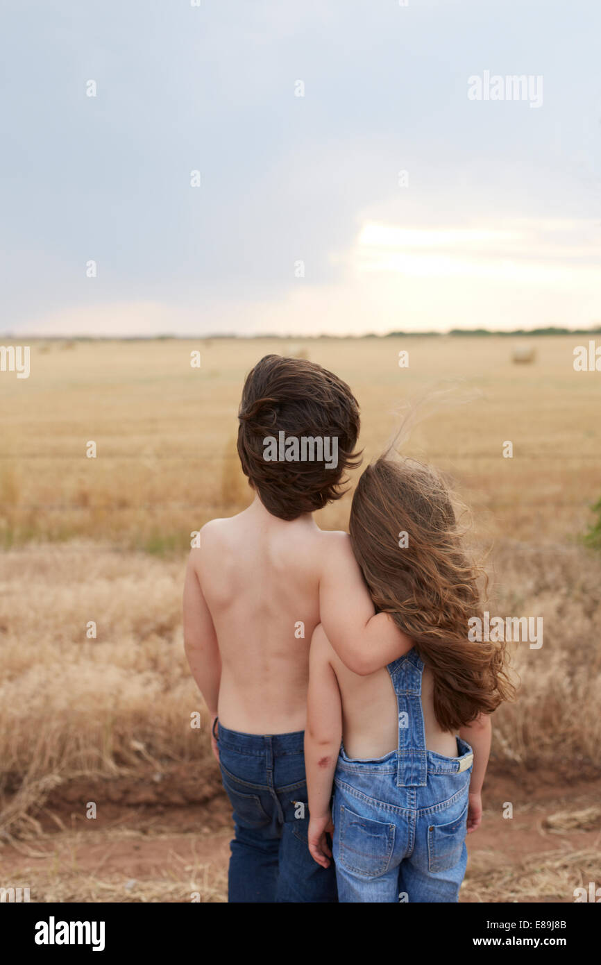 Boy and girl overlooking country field - Stock Image