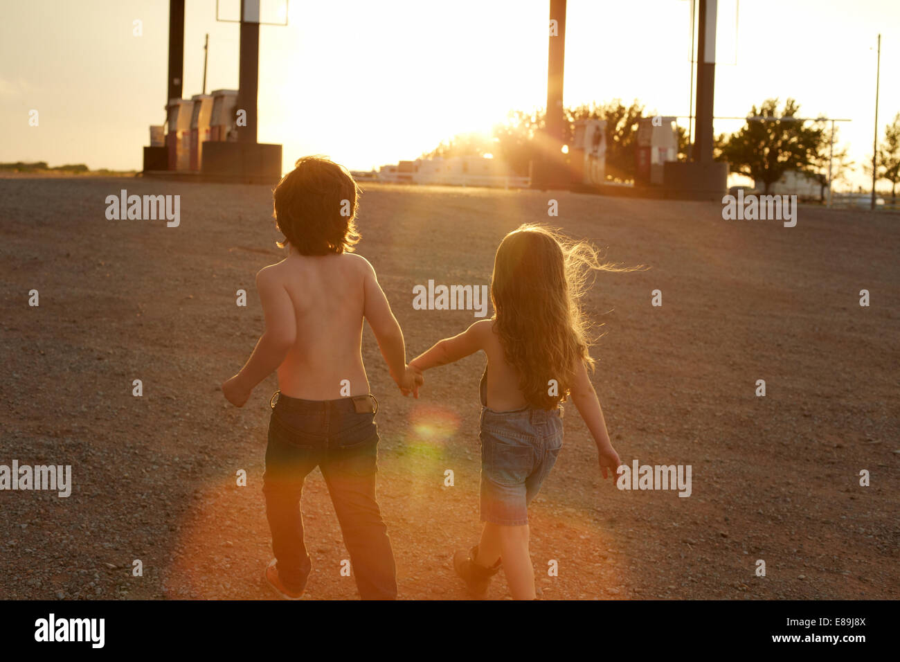 Siblings holding hands at gas station - Stock Image