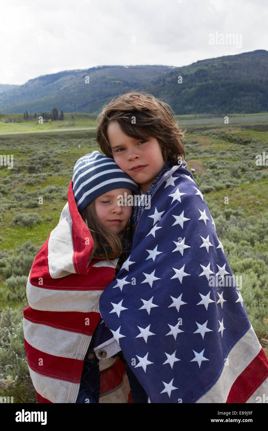 Brother and sister wrapped in American flag in field - Stock Image