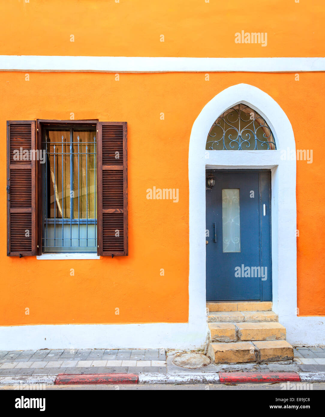Fragment of a building in Tel Aviv, Israel with a door and a window - Stock Image