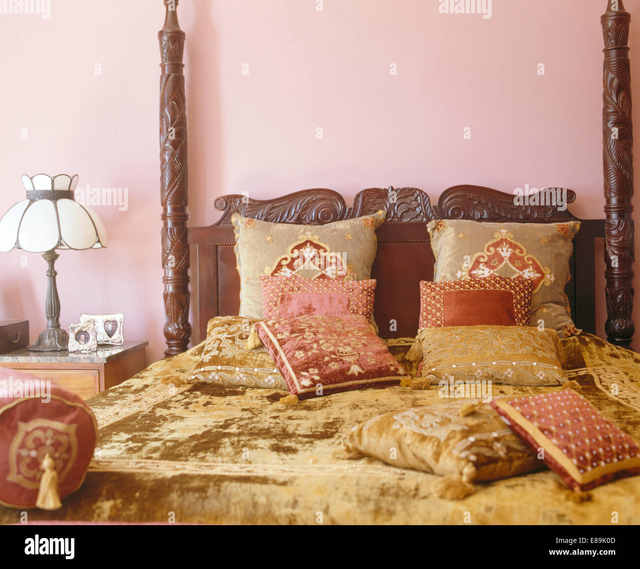 Light brown chenille bedcover and cushions on carved wooden bed in ...