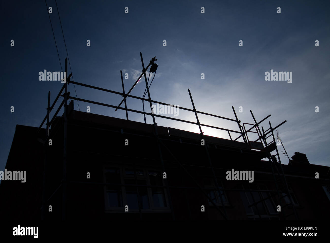 A silhouette of scaffolding on a house - Stock Image