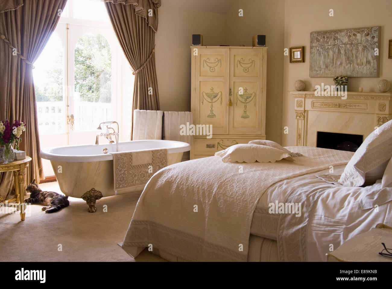 Rolltop bath in country bedroom with cream linen on bed and painted