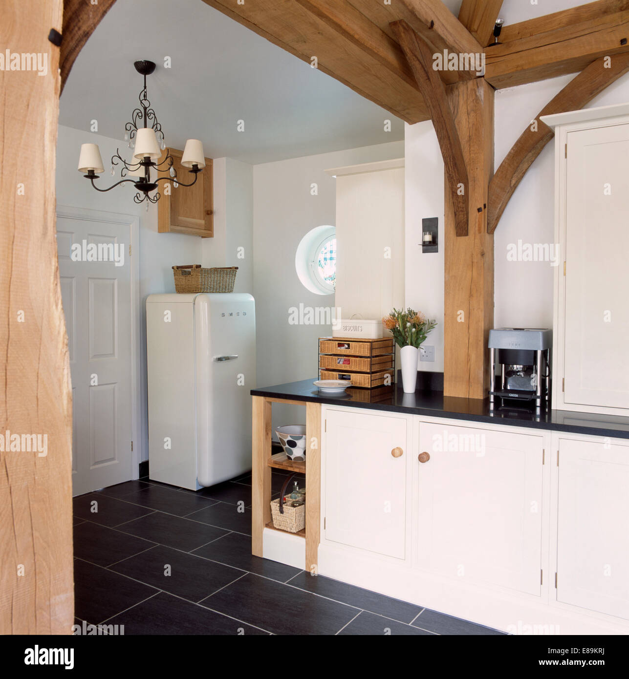 Large Wooden Beams In Barn Conversion Kitchen With Smeg Fridge And Slate  Flooring