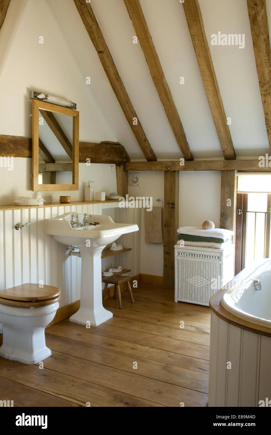 Mirror above pedestal washbasin in country bathroom with wooden ...
