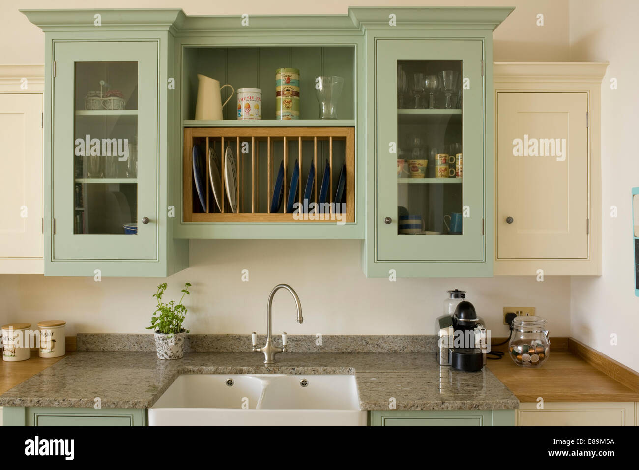 Pale green wall cupboard above double sink in country kitchen Stock ...
