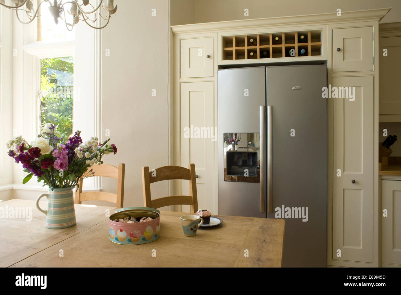 Vase of summer flowers on table in country kitchen with wine storage above American style fridge freezer Stock Photo