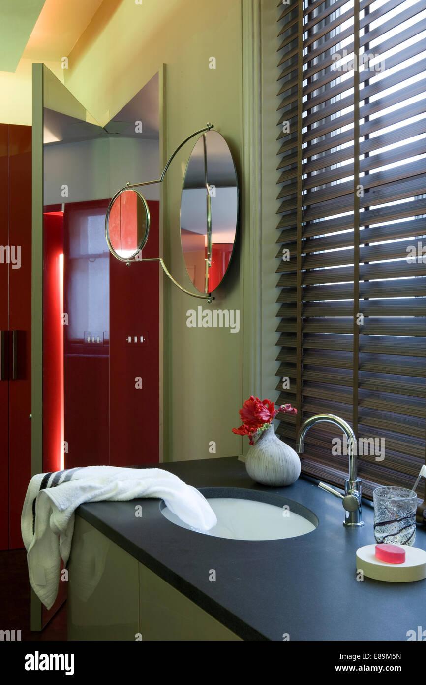 Venetian blind above washbasin in vanity unit in modern green bathroom - Stock Image