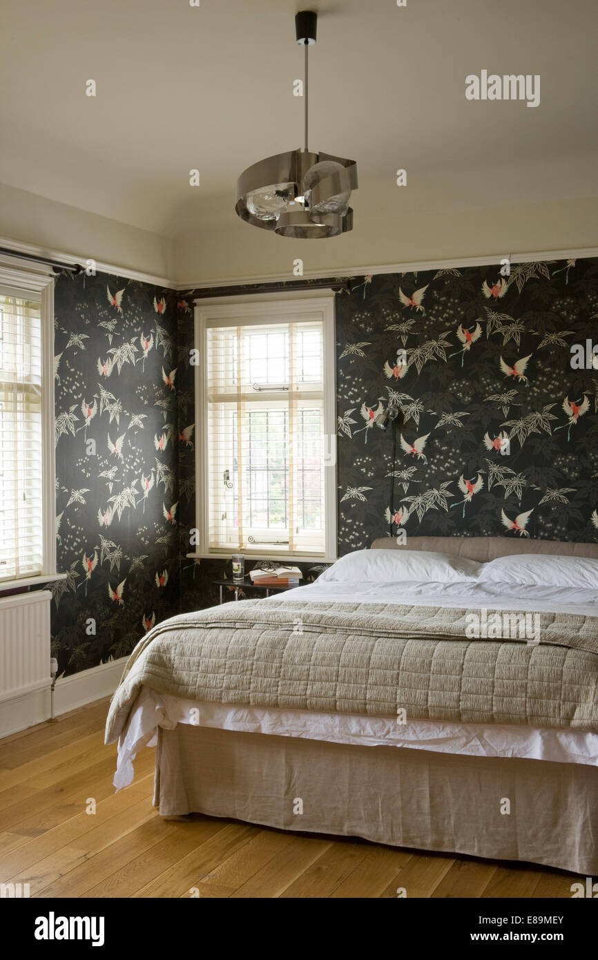 . Grey floral patterned wallpaper in modern bedroom with beige silk