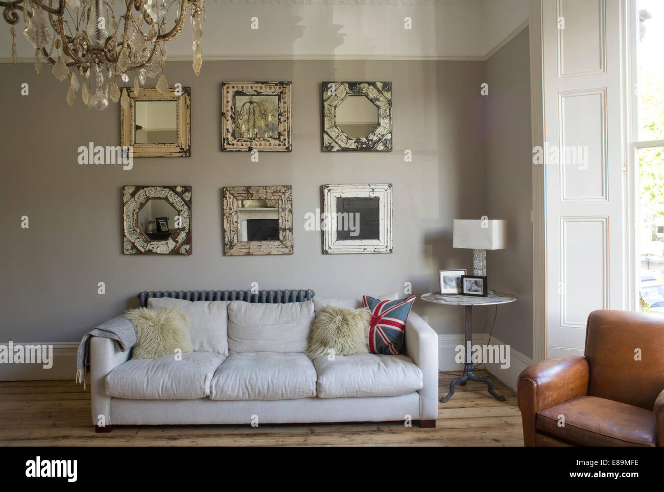 Collection Of Ornate Mirrors Above White Sofa In White Country Sitting Room