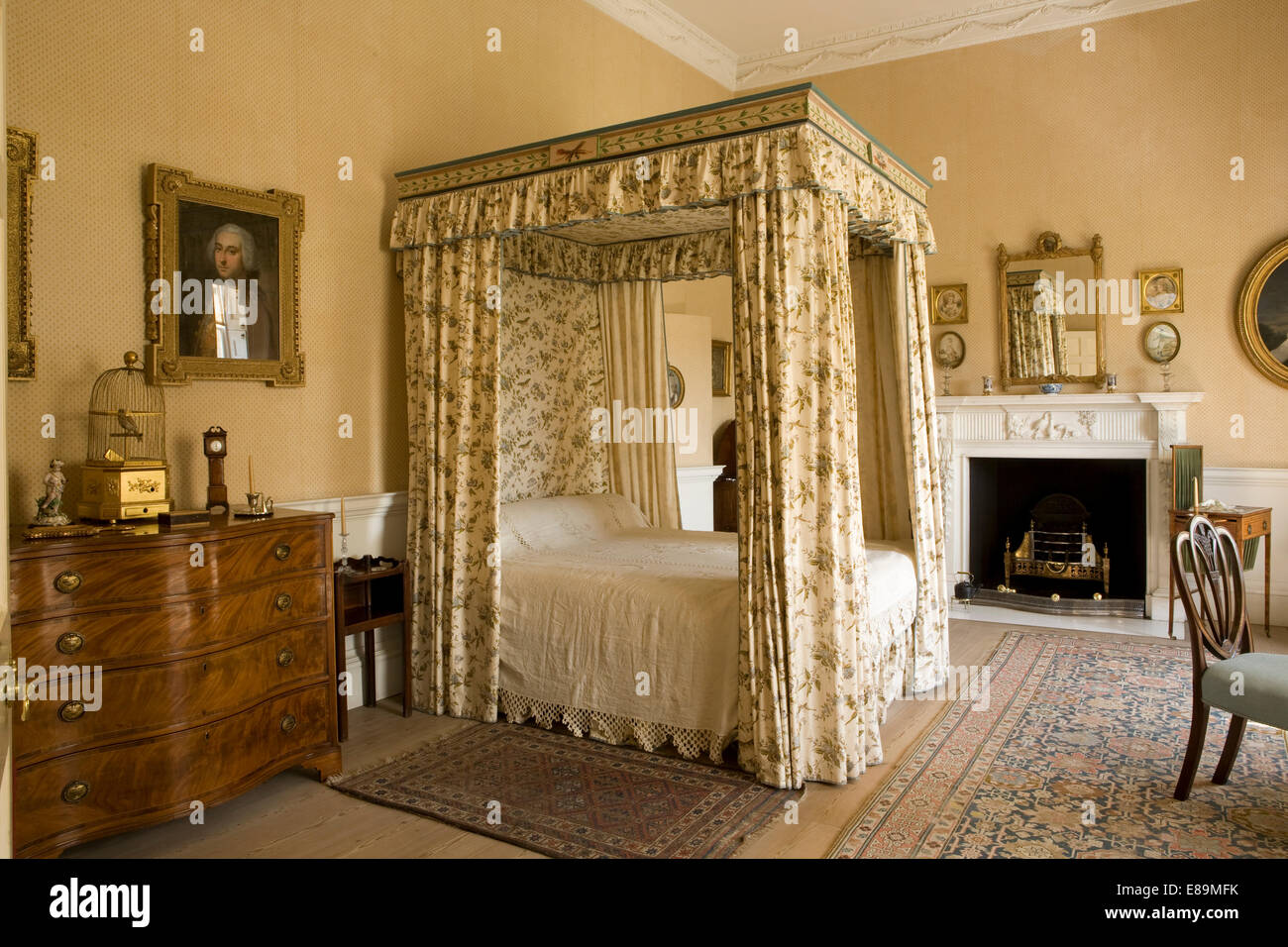 Floral drapes and canopy on four poster bed in country house bedroom - Stock Image