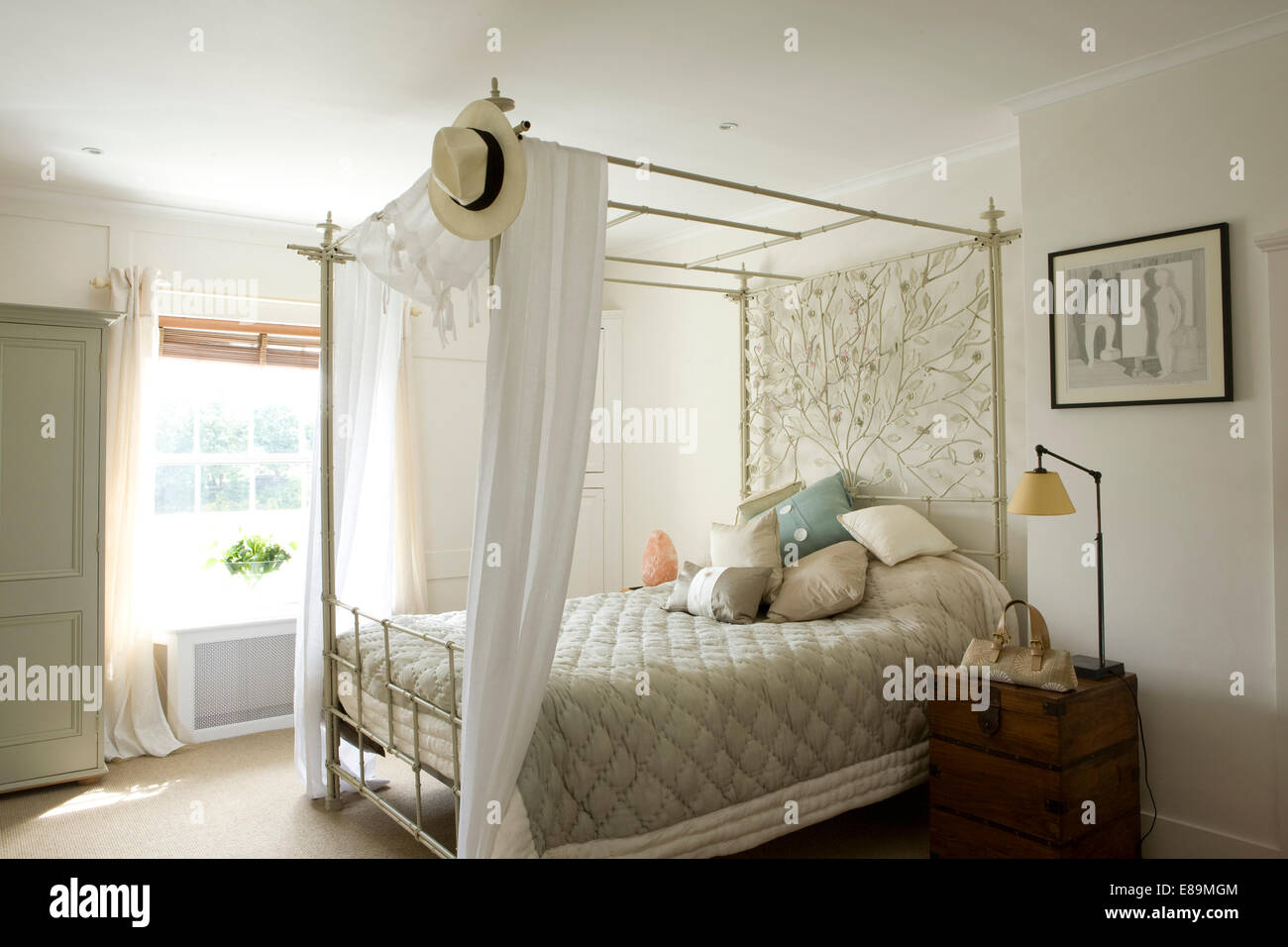 White Cotton Drapes On Four Poster Bed With Ornate Metalwork Panel In Country Bedroom