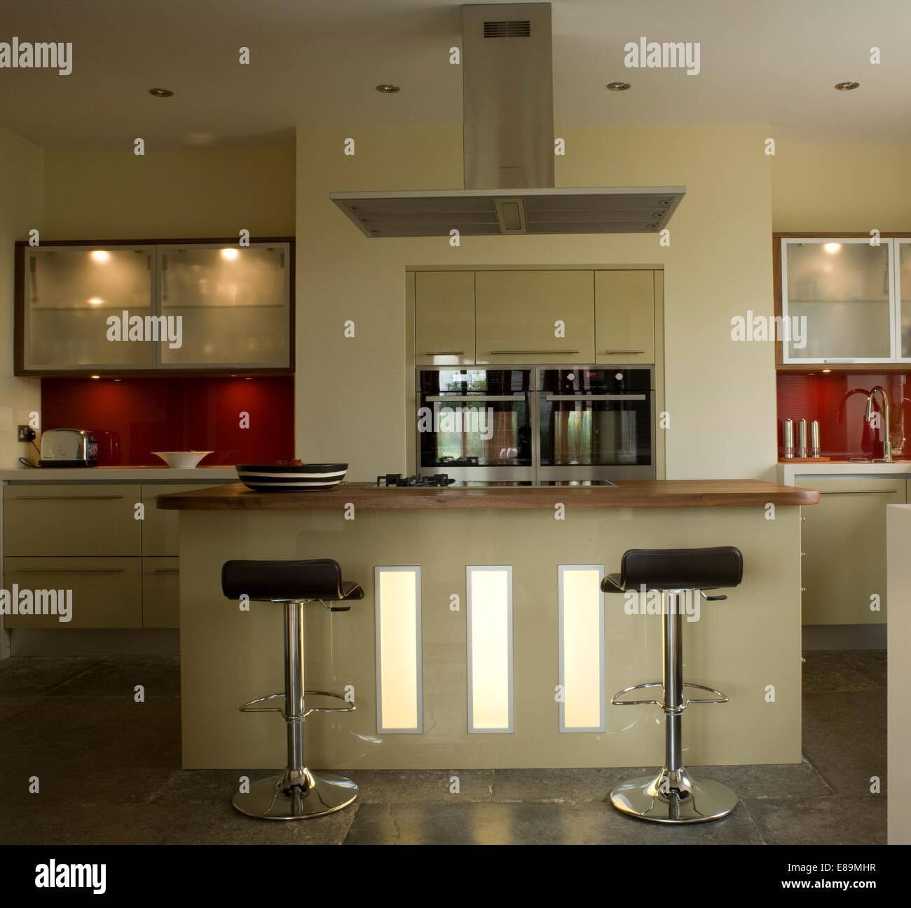 Bar stools at central island breakfast bar in modern kitchen with ...
