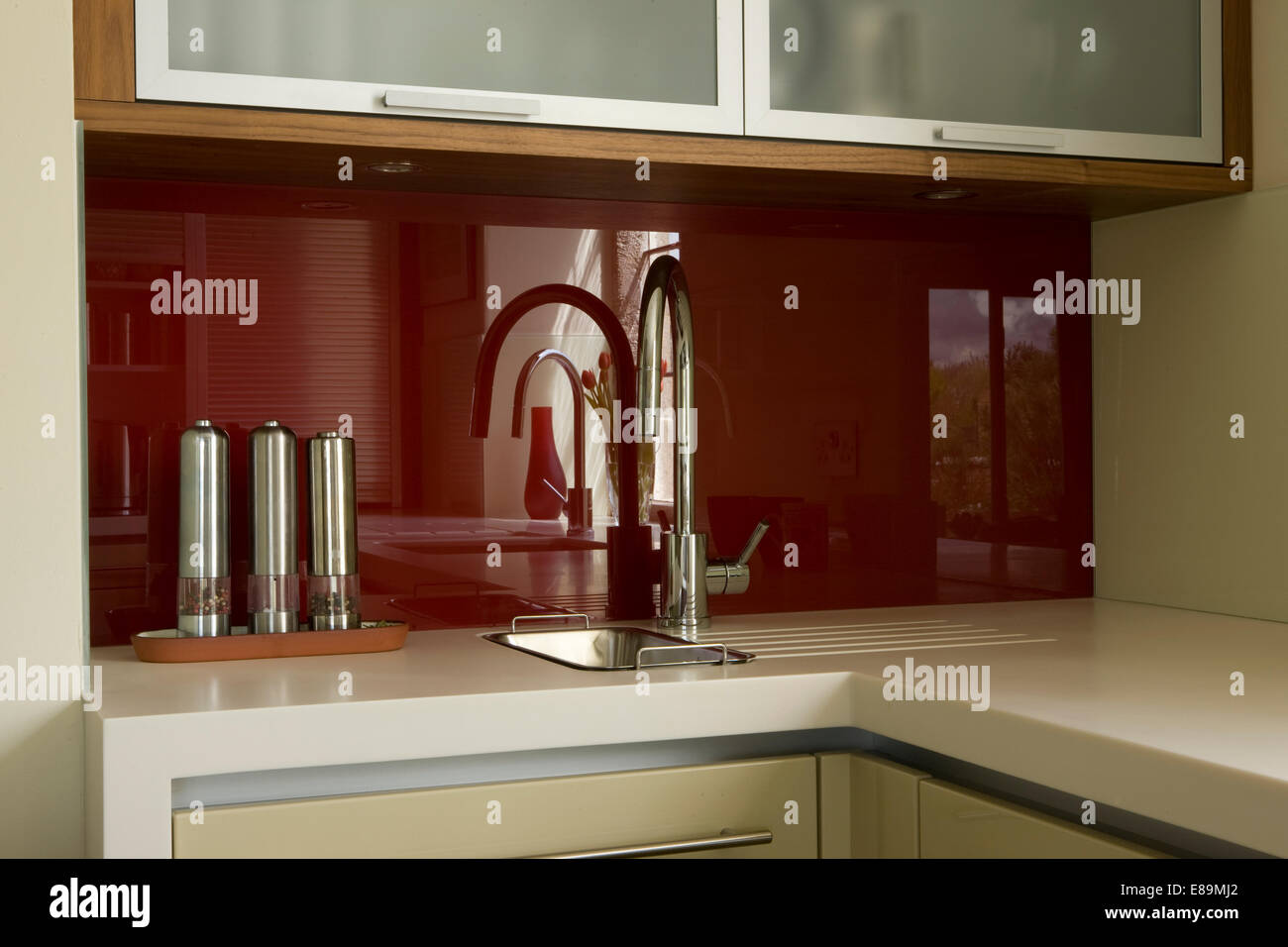 Chrome pepper and salt mills beside chrome tap at miniature sink - Stock Image